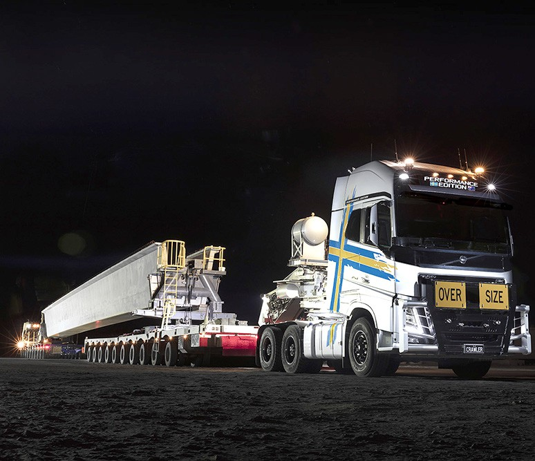 Oversize over mass vehicle at night loaded with super t girder